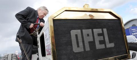Opel-Chef Nick Reilly besteigt einen Oldtimer von 1903.