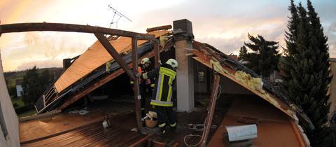 Feuerwehrleute arbeiten am Dachstuhl eines beschädigten Hauses
