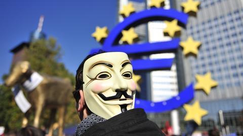 Protestler vor der Euro-Statue in Frankfurt