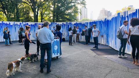 Menschen vor einer weißen Leinwand mit blauen Strichen.
