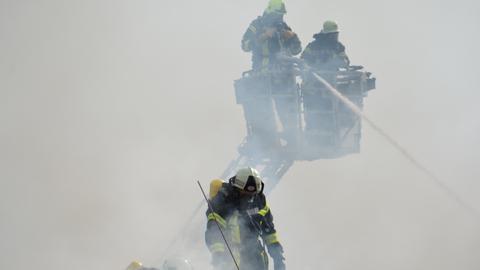 Feuerwehrleute bekämpfen die Flammen von einer Leiter aus.