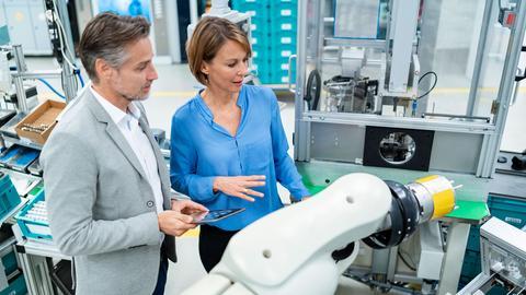 Frau zeigt Mann in Produktionshalle den Ablauf