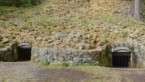Zwei vergitterte Eingänge in einem Berg