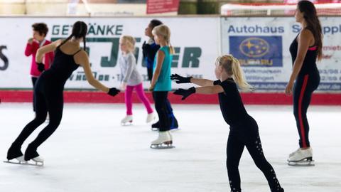 Junge Leute mit Schlittschuhen auf der Eisfläche