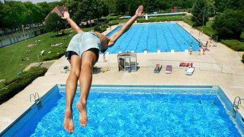 Ein Junge springt von einem Turm in ein Freibad.