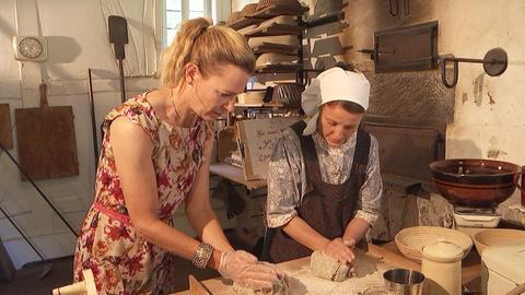 Zwei Frauen backen auf historische Weise Brot im Hessenpark.