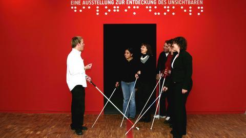 Menschen mit Blindenstöcken stehen vor dem Eingang des Dialogmuseums.