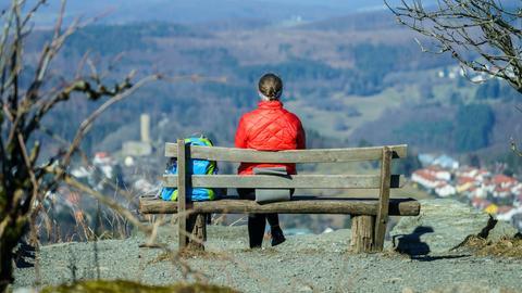 Eine Frau sitzt mit Blick auf die Burg Reifenberg auf einer Bank auf dem Feldberg-Plateau.
