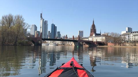Ein rotes Boot auf dem Main - im Hintergrund die Frankfurter Skyline