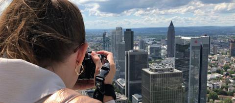 Reporterin Alisa Schmitz ist auf der Suche nach dem perfekten Blick auf die Frankfurter Skyline.