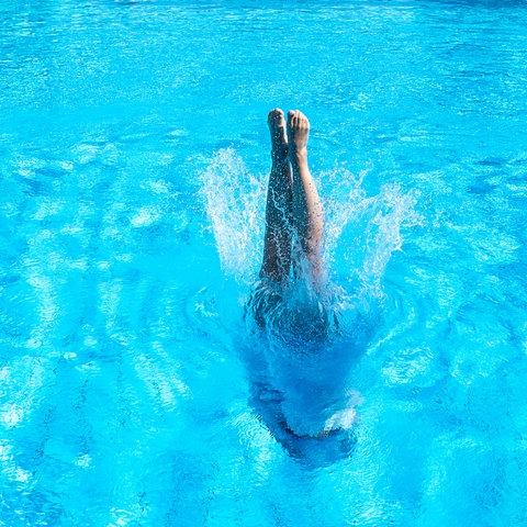 Eine Frau taucht in ein leeres Schwimmbecken ein. Nur noch ihre Füße sind zu sehen.