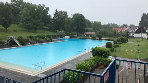 Ein leeres Schwimmbecken mit Absperrband