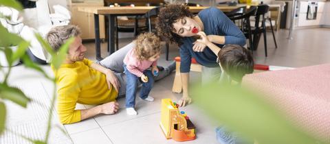 Familie spielt auf dem Boden im Wohnzimmer