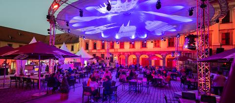 Gäste sitzen während einer Veranstaltung der Genusswochen im Innenhof des Fuldaer Stadtschlossses.