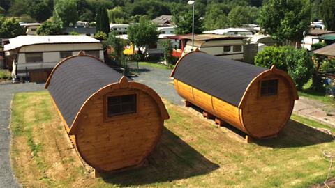 Komfortable Wohnfässer vor gewöhnlichen Wohnwagen auf dem Campingplatz Weilburg-Odersbach