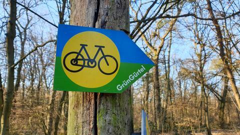 Hinweisschild auf Grüngürtel-Radweg im winterlichen Wald