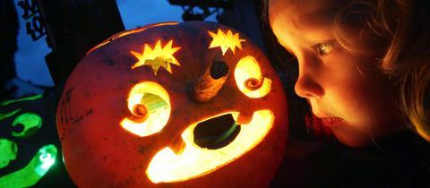 Trauriges Kind mit Halloween-Kürbis
