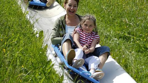 Mutter und Tochter auf der Sommerrodelbahn