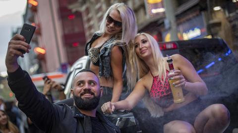 Ein Mann macht ein Selfie mit zwei Frauen bei der Bahnhofsviertelnacht.