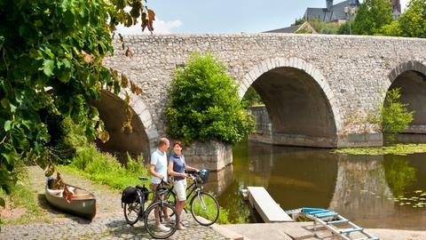 Paar mit Fahrrädern am Ufer der Lahn