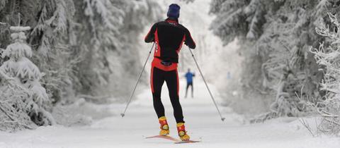 Langläufer skaten auf der Loipe auf dem nordhessischen Hohen Meissner in einer vor Eis und Schnee starrenden Winterlandschaft.