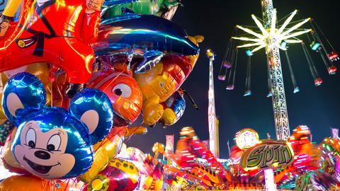 Bunte Eindrücke von einem Jahrmrkt mit fliegendem Karusell, Luftballons und weiteren Fahrgeschäften.