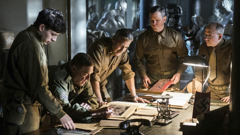 Fünf Männer in Uniform stehen um einen Schreibtisch