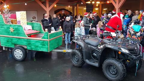 Weihnachtlich geschmückter Schlitten, gezogen von Krad, im Hintergrund Nikolaus mit Menschen