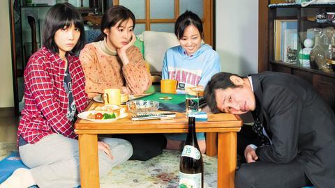 Eine japanische Familie am Tisch, der Mann hat den Kopf auf die Tischplatte gelegt