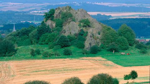 Der Scharfenstein ragt wie ein karger Fels aus Feldern im Schwalm-Eder-Kreis. Im Vordergrund sind abgeerntete Felder zu sehen, der Fels ist im unteren Drittel bewaldet. Im Hintergrund tauchen kleine Ortschaften auf.