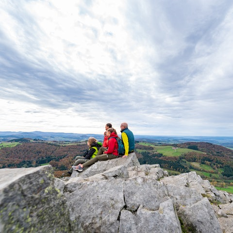 Eine Familie sitzt auf einem Hügel