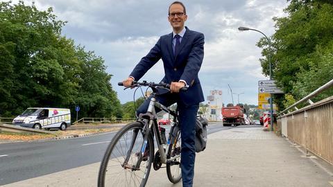 Der Fuldaer Stadtbaurat Daniel Schreiner sitzt auf seinem Fahhrrad nahe der Brücken-Baustelle