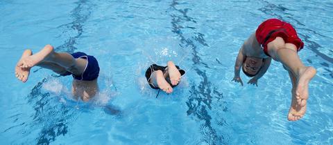 Kinder springen in ein Schwimmbecken
