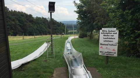 Hinweisschild an der Sommerrodelbahn Hoherodskopf und Ausblick in den Vogelsberg