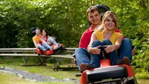 Ein junges Paar auf der Sommerrodelbahn Silbersee