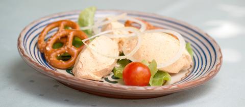 Drei eiergroße Kleckse Spundekäse auf einem Teller, garniert mit Tomate und Brezel