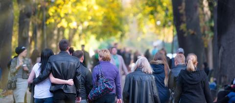 Menschen laufen durch eine herbstliche Allee.