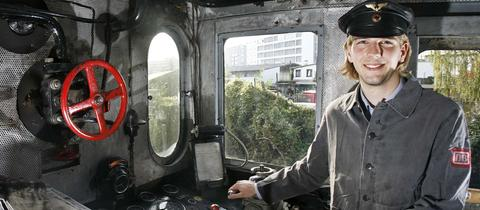 Das Bild zeigt einen jungen Lokführer in einer grauen Uniform. Er steht im Führerstand und lacht, im Hintergrund sind Hebel und Knöpfe der Lok zu sehen
