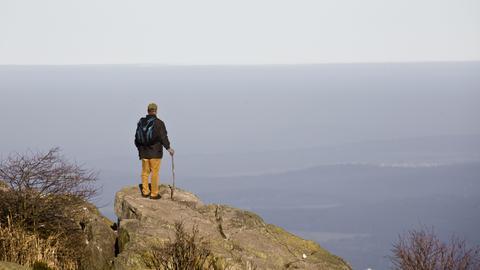 Ein Wanderer steht auf einem Felsen und blickt über die Landschaft