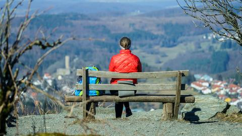 Frau sitzt auf einer Bank und blickt auf die Burg Reifenberg