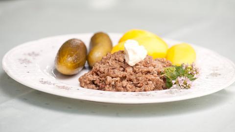 Auf einem Teller serviert: Weckewerk mit zwei sauren Gurken und mehreren Pellkartoffel