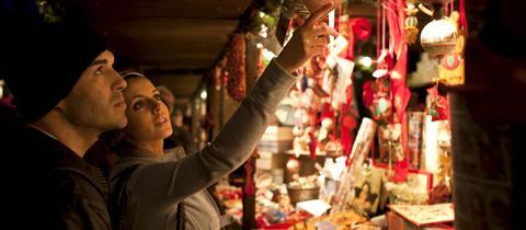 Pärchen auf einem Weihnachtsmarkt vor einem Stand