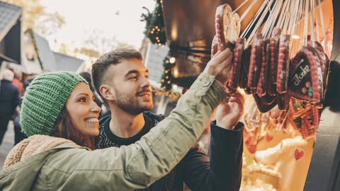 Pärchen auf einem Weihnachtsmarkt vor einem Lebkuchenbüdchen