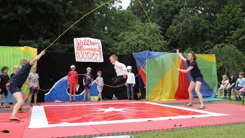 Kinder springe in Zirkuskulisse Springseil