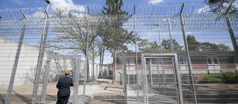 Eine Justizbeamtin geht auf einen hohen Zaun im neuen Abschiebegefängnis in Darmstadt zu.