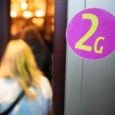 """Ein pinkfarbener Aufkleber mit der gelbern Aufschrift """"2G"""" ist an einer Eingangstür zu sehen."""