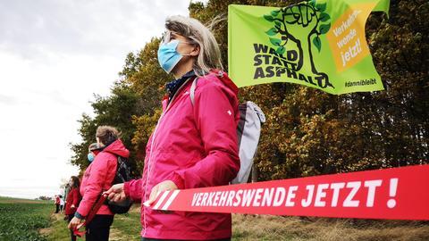 Frau mit Mundschutz steht in einer Menschenkette