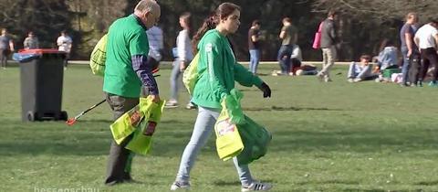 Mitarbeiter von #cleanffm helfen beim Aufräumen im Grüneburgpark.