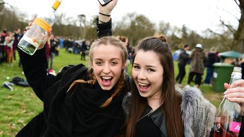 Zwei Schülerinnen feiern im Park mit Alkoholflaschen in der Hand