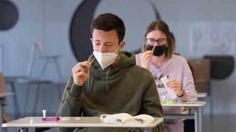 Ein Schüler und eine Schülern führen einen nasalen Selbsttest in der Schule durch.
